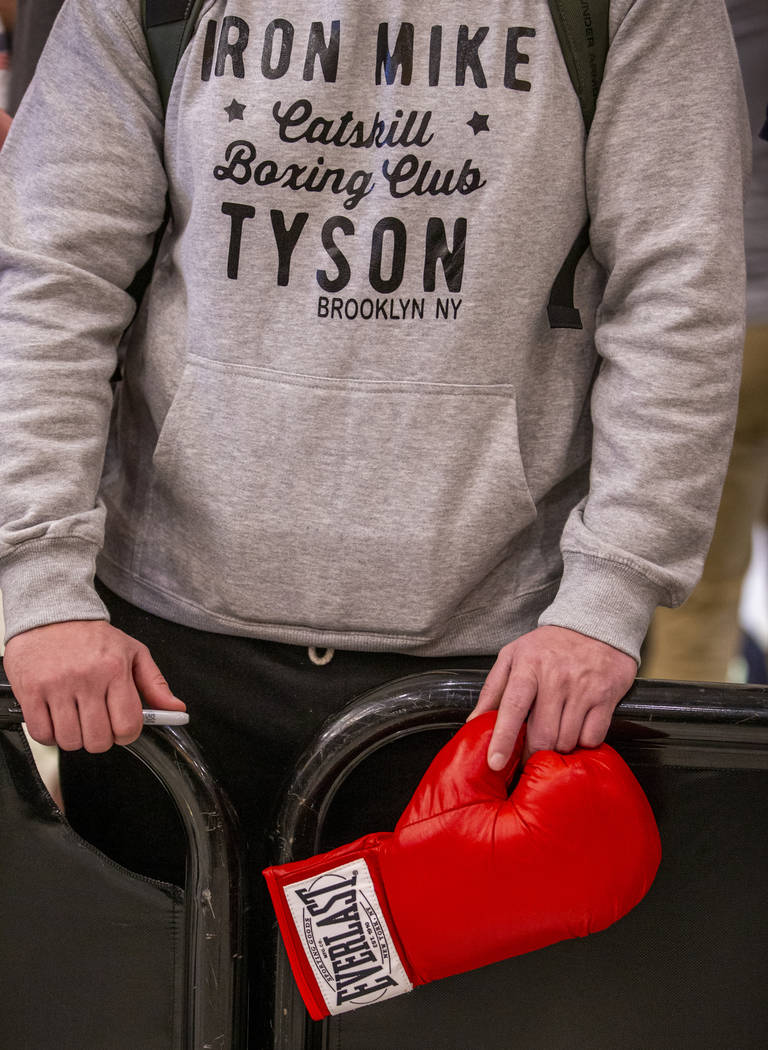 A fan holds a boxing glove in hopes of an autograph from WBC heavyweight title fighter's Tyson ...