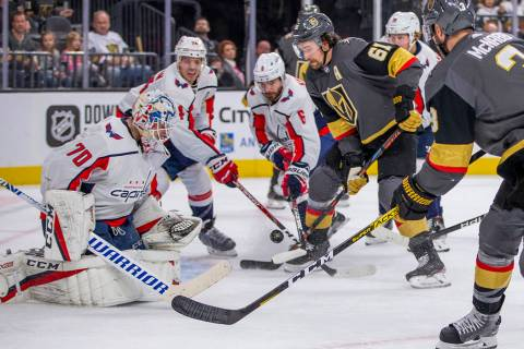 Vegas Golden Knights right wing Mark Stone (61, center) battles for a shot on Washington Capita ...