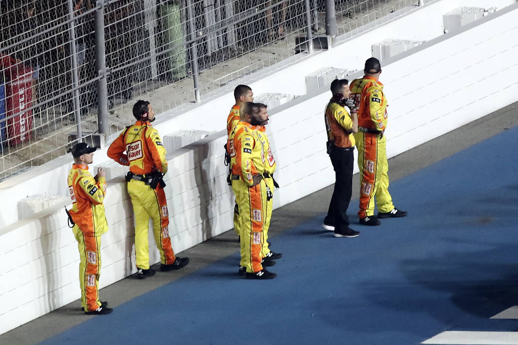 Ryan Newman's crew stands near a wall on pit road as they are kept back from rescue workers tha ...