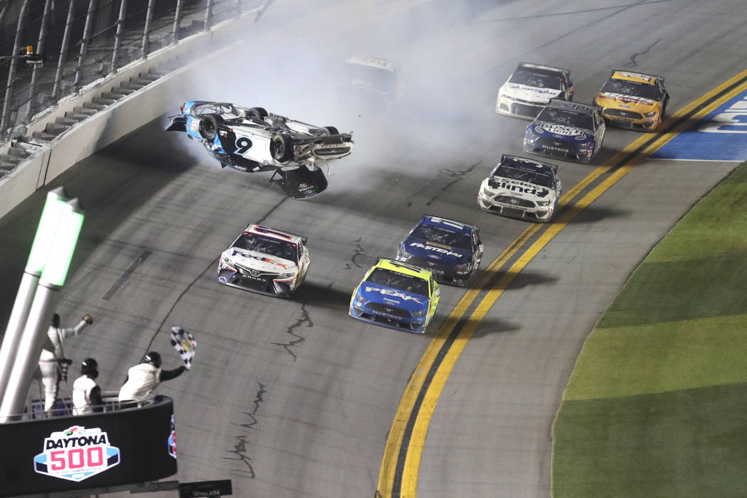 Denny Hamlin, front left, passes Ryan Blaney, front right on the way to the finish line to win ...