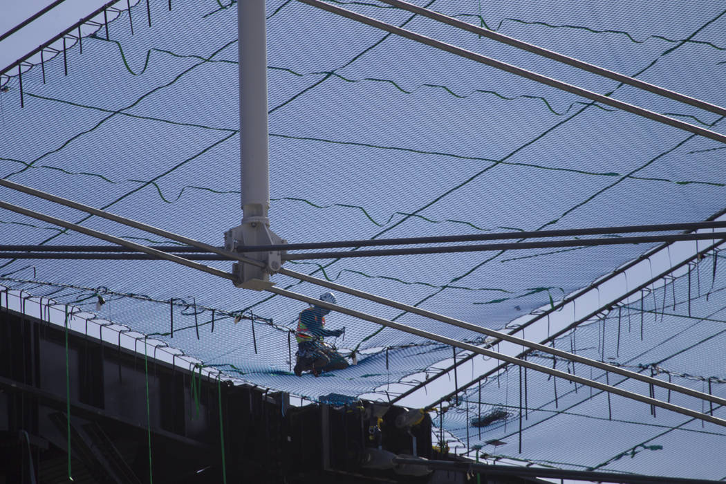 Netting is installed on top of the steel cable net system at the Raiders Allegiant Stadium in L ...