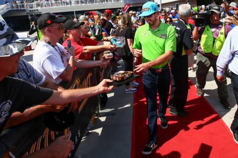 Kyle Busch gives autographs to fans before a NASCAR Cup Series auto race at Las Vegas Motor Spe ...
