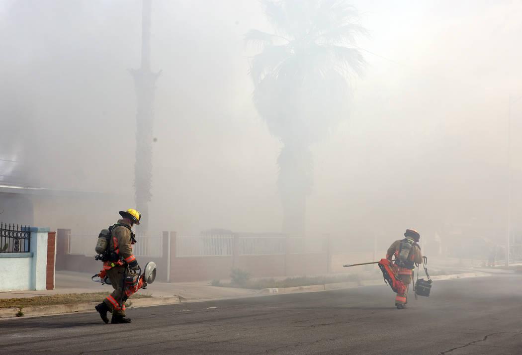 Heavy smoke is seen as Las Vegas firefighters prepare to battle a house fire at 2417 Howard Dri ...