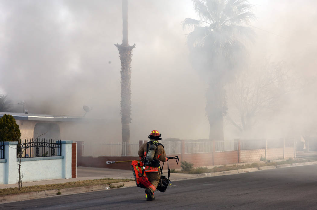 Heavy smoke is seen as a Las Vegas firefighter prepares to battle a house fire at 2417 Howard D ...