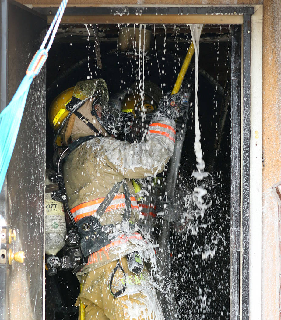 A Las Vegas firefighter battles a house fire at 2417 Howard Drive on Tuesday, Feb. 18, 2020, in ...