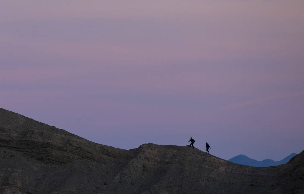 People, as seen looking east from Zabriskie Point, make their way up a ridge before sunset in D ...