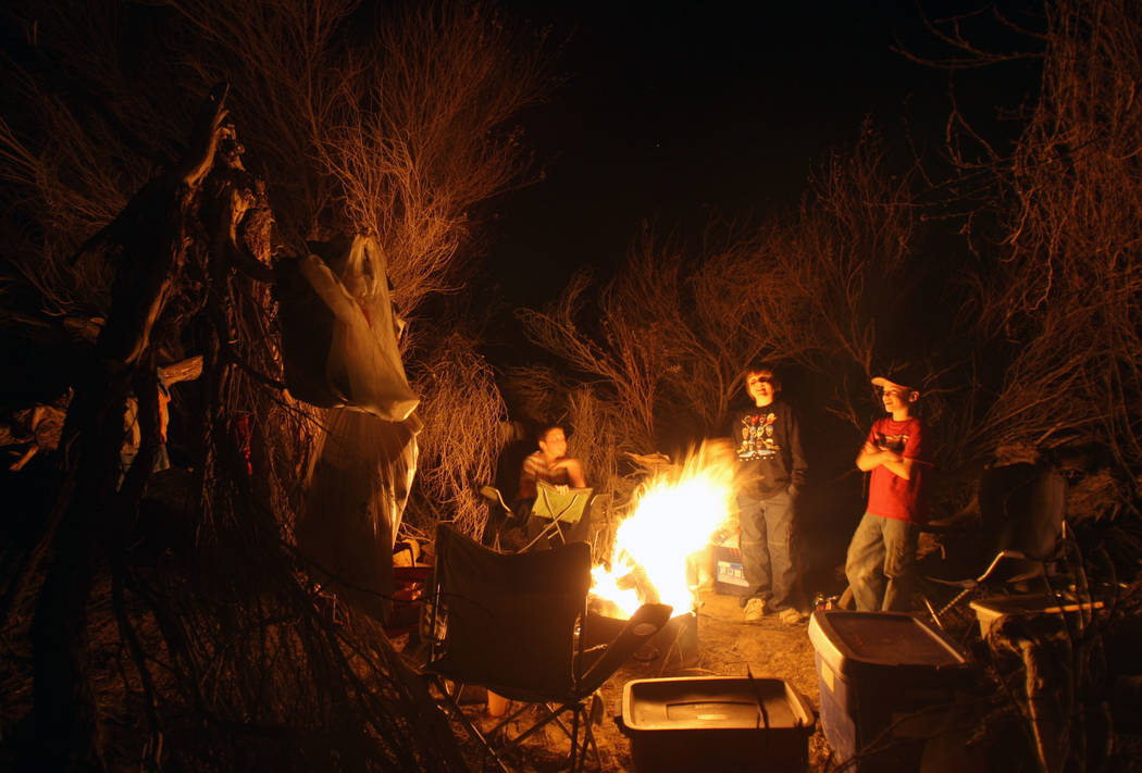 Children gather around a campfire while camping in Saline Valley at Death Valley National Park. ...