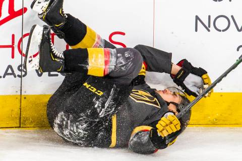 Vegas Golden Knights defenseman Zach Whitecloud (2) hits his head on the boards after being tri ...