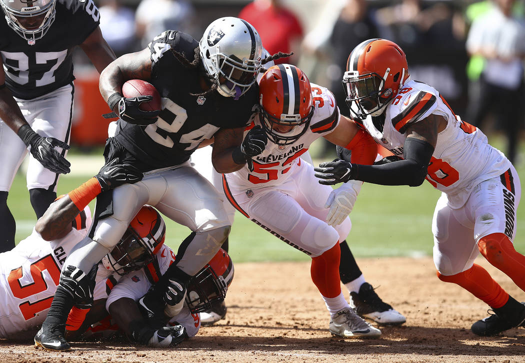 Oakland Raiders running back Marshawn Lynch (24) is stopped by Cleveland Browns outside linebac ...