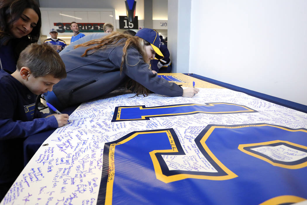 Fans sign a banner sending well wishes to St. Louis Blues' Jay Bouwmeester prior to the start o ...