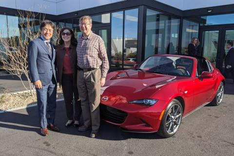 Mazda North American Operations chairman and CEO Masahiro Moro, left, poses with a couple who p ...