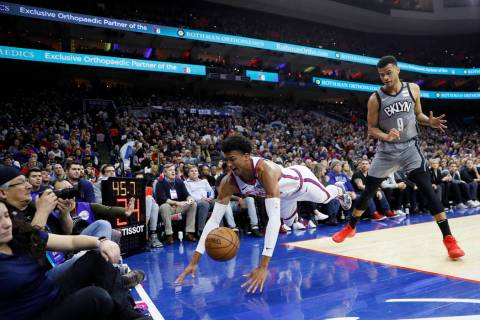 Philadelphia 76ers' Matisse Thybulle, center, dives for a loose ball past Brooklyn Nets' Timoth ...