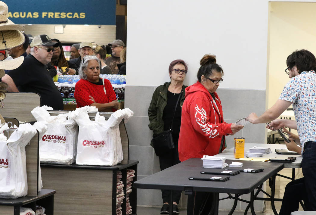 Nation Graca, right, site leader, hands out voting card to Renee Cazares of Las Vegas, during t ...