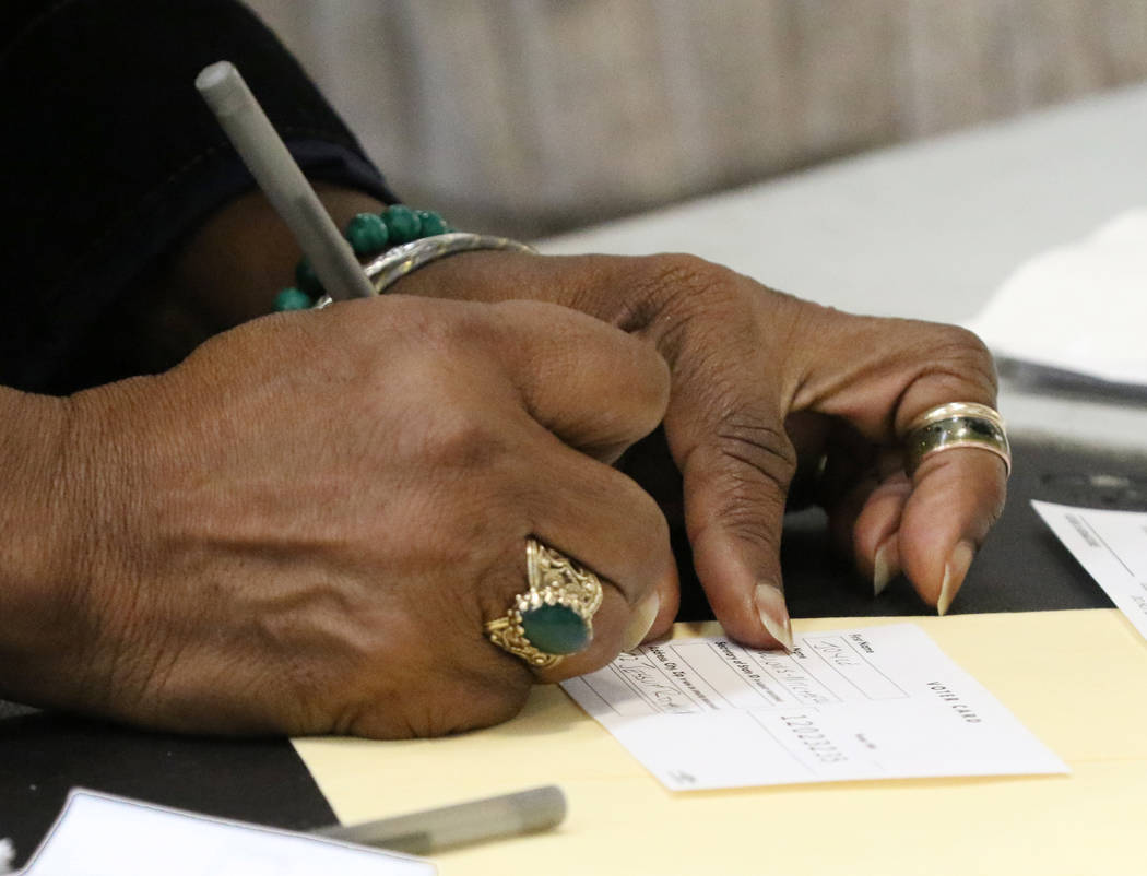 Joyce Williams-Mitchell fills out her voting card during the last day of early voting in the Ne ...