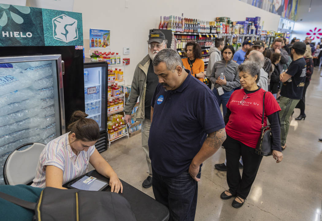 Individuals sing in to cast their early vote at Cardenas Market in Las Vegas on Tuesday, Feb. 1 ...