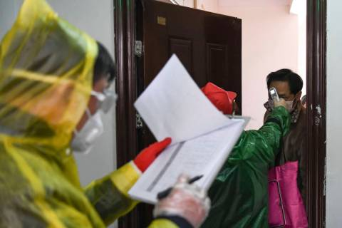 In a Feb. 18, 2020, photo released by Xinhua News Agency, workers go door to door to check the ...