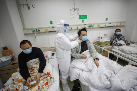 A doctor checks the conditions of a patient in Jinyintan Hospital, designated for critical COVI ...