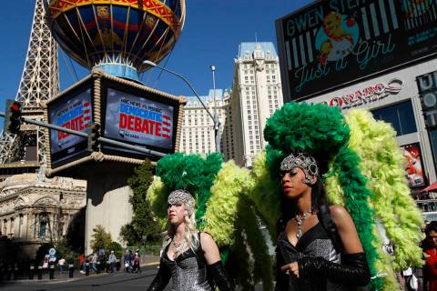 Women dressed as showgirls walk near the Paris Las Vegas, site of a Democratic presidential deb ...