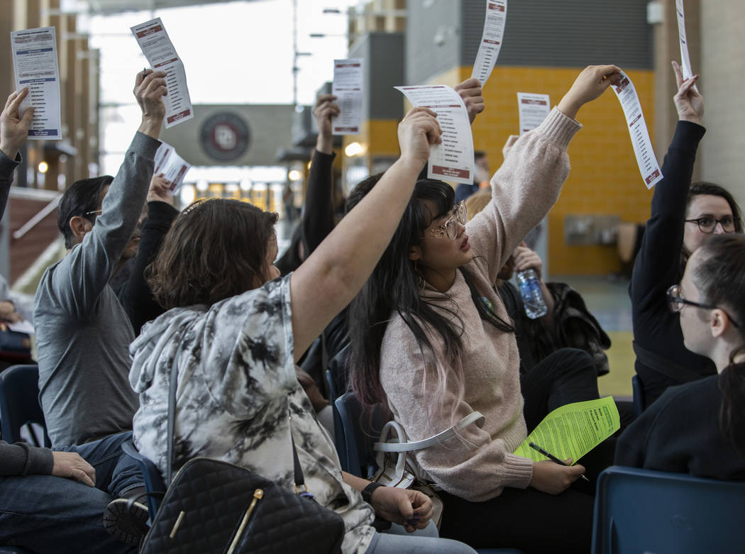 Bernie Sanders supporters hold up their ballots during he first alignment of their group during ...