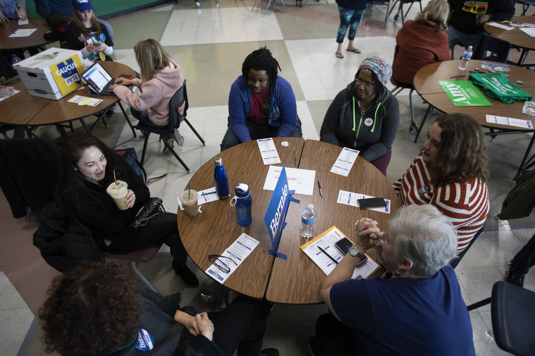 Bernie Sanders supporters chat at their table before the Nevada caucus begins at Palo Verde Hig ...