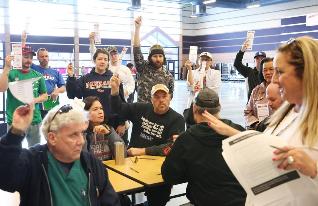 Lori Church, right, precinct chair, counts as Democratic caucus-goers raise their voting cards ...