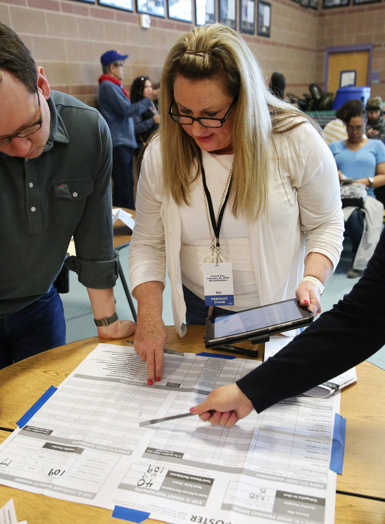 Lori Church, center, precinct chair, logs voting result on caucus math poster after Democratic ...