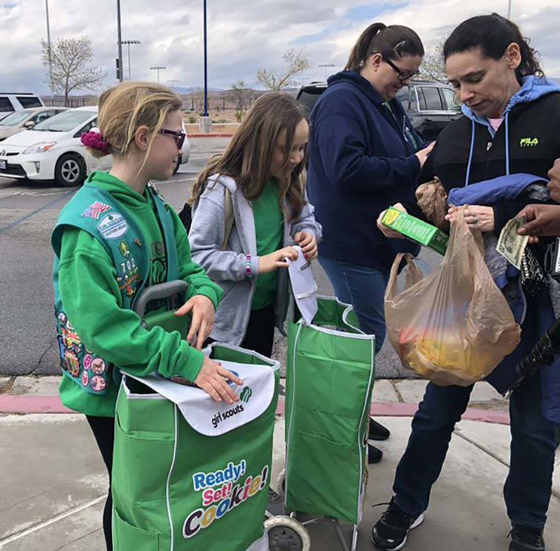 Girl Scouts sell cookies to those attending the Nevada Democratic caucuses at Sierra Vista High ...