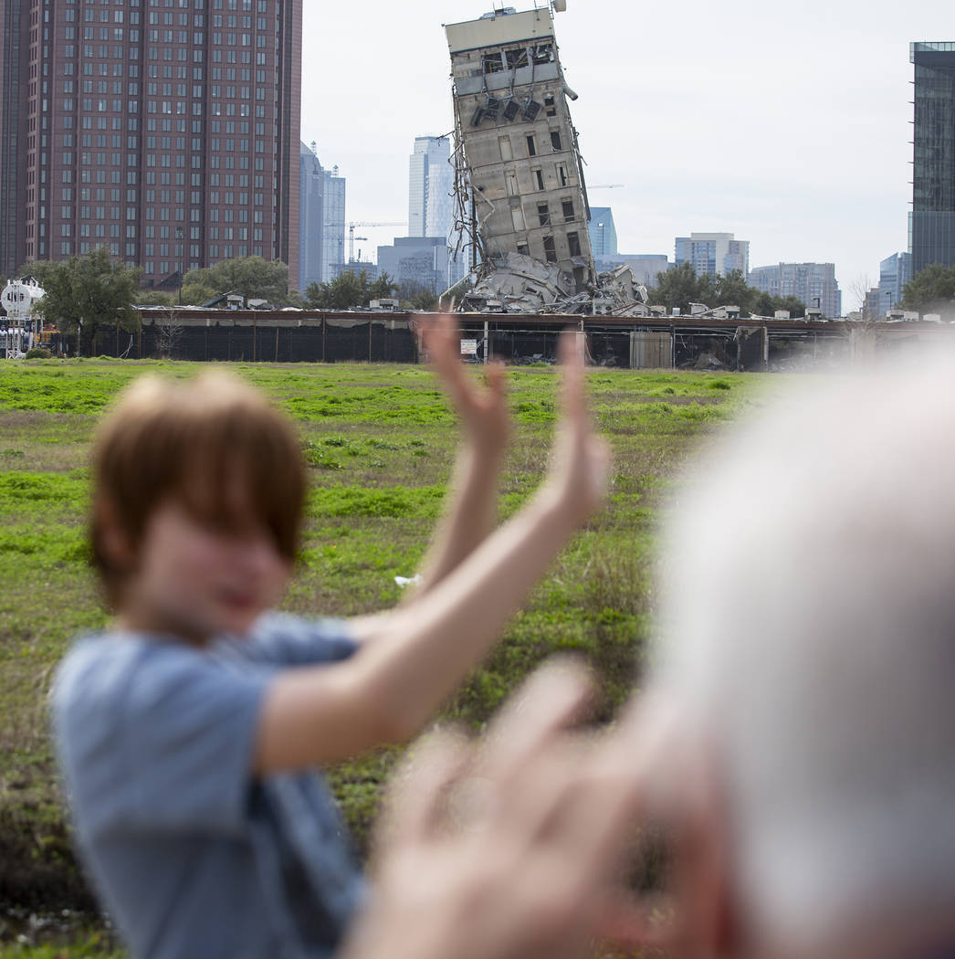 Randy Gibson takes a photo of his son Andrew, 11, in front of the 'Leaning Tower of Dallas' on ...