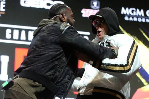 Deontay Wilder, left, shoves Tyson Fury during a press conference at the MGM Grand Garden Arena ...