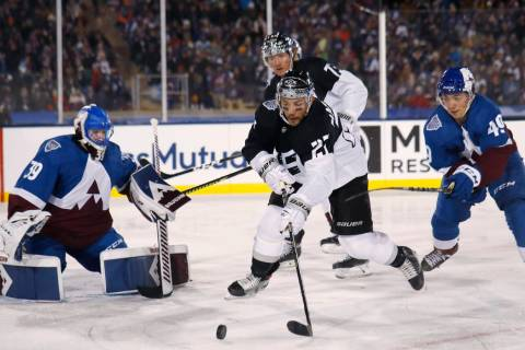 Los Angeles Kings defenseman Alec Martinez, center, looks to redirect the puck, between Colorad ...