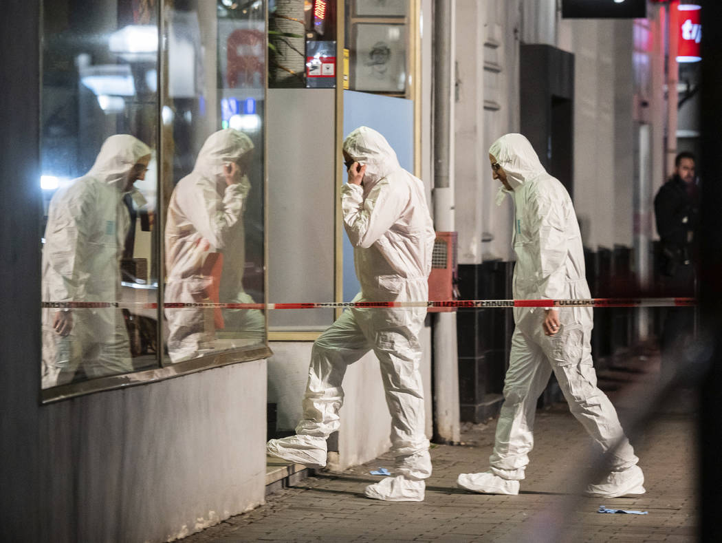 Forensics enter a building at the scene after a shooting in central Hanau, Germany Thursday, Fe ...