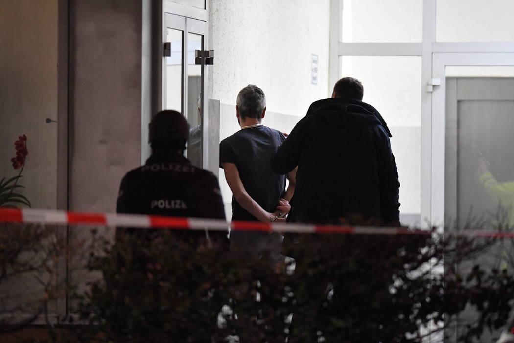 Police handcuff a man near the scene of a shooting in Hanau, Germany early Thursday, Feb. 20, 2 ...