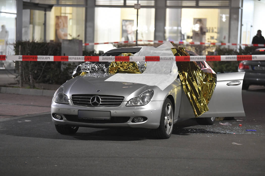 A car that was damaged in a shooting is covered in thermo foil is parked in front of a bar at t ...