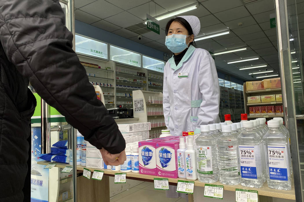 A pharmacy worker attends to visitors at the store entrance in Beijing, China on Thursday, Feb. ...