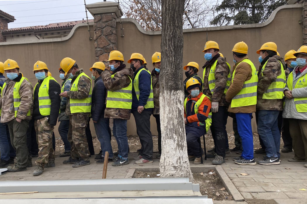 Workers line up for lunch outside a construction site of a hospital as part of plans to fight a ...
