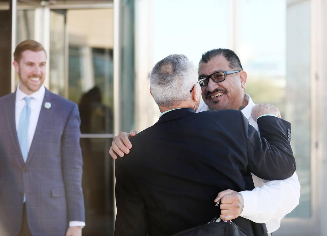Attorney Shawn Perez, left, hugs defendant Pastor Palafox outside the Lloyd George U.S. Courtho ...