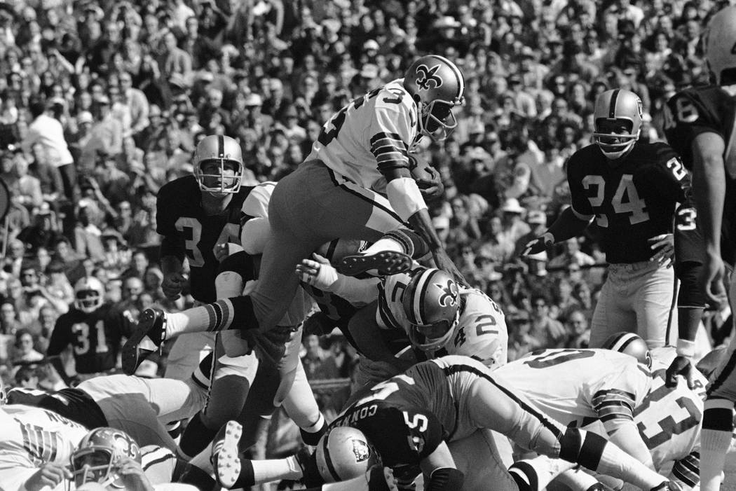 New Orleans Saints running back Bob Gresham (35) takes to the air for a first down over teammat ...