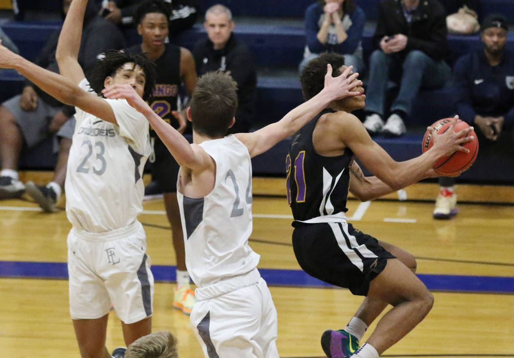 Durango High's Anthony Hunter (21) fouled by Faith Lutheran's Coleman Lemke (24) as he goes for ...