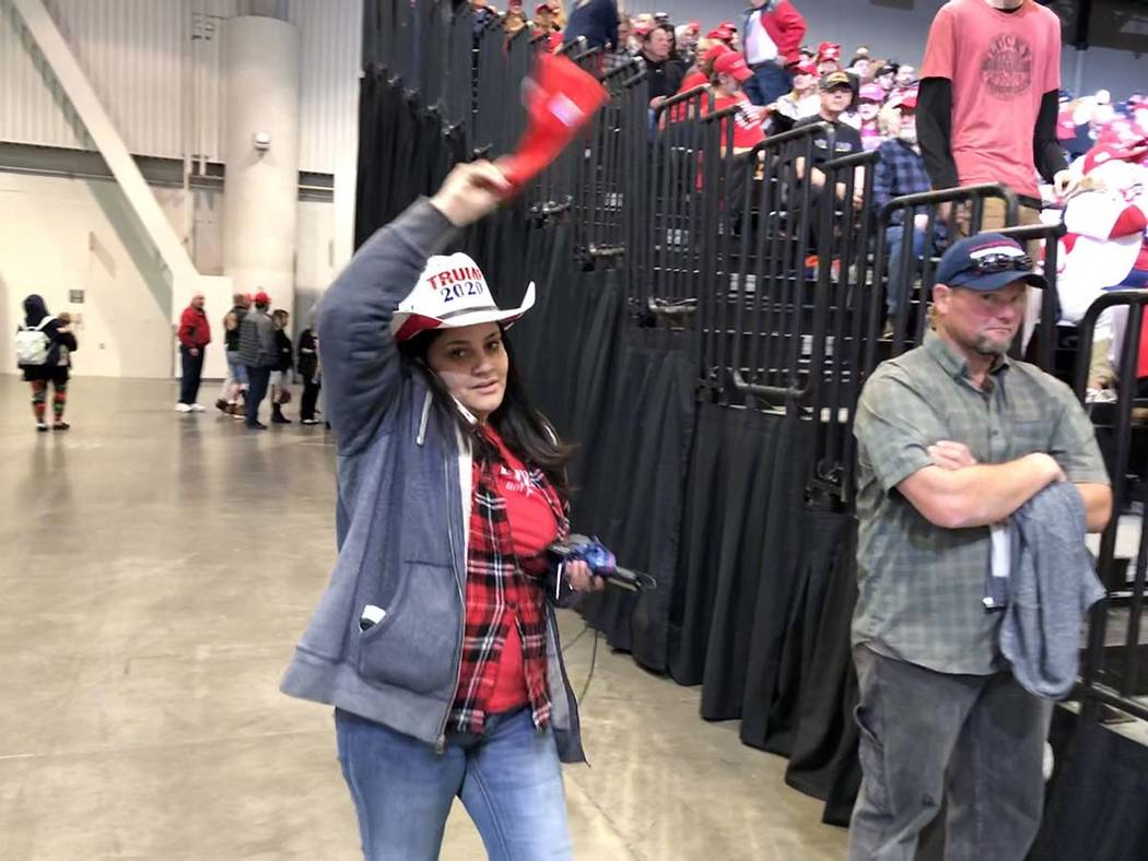 One woman waves a Trump hat while on the phone, seemingly trying to find someone in the crowd. ...