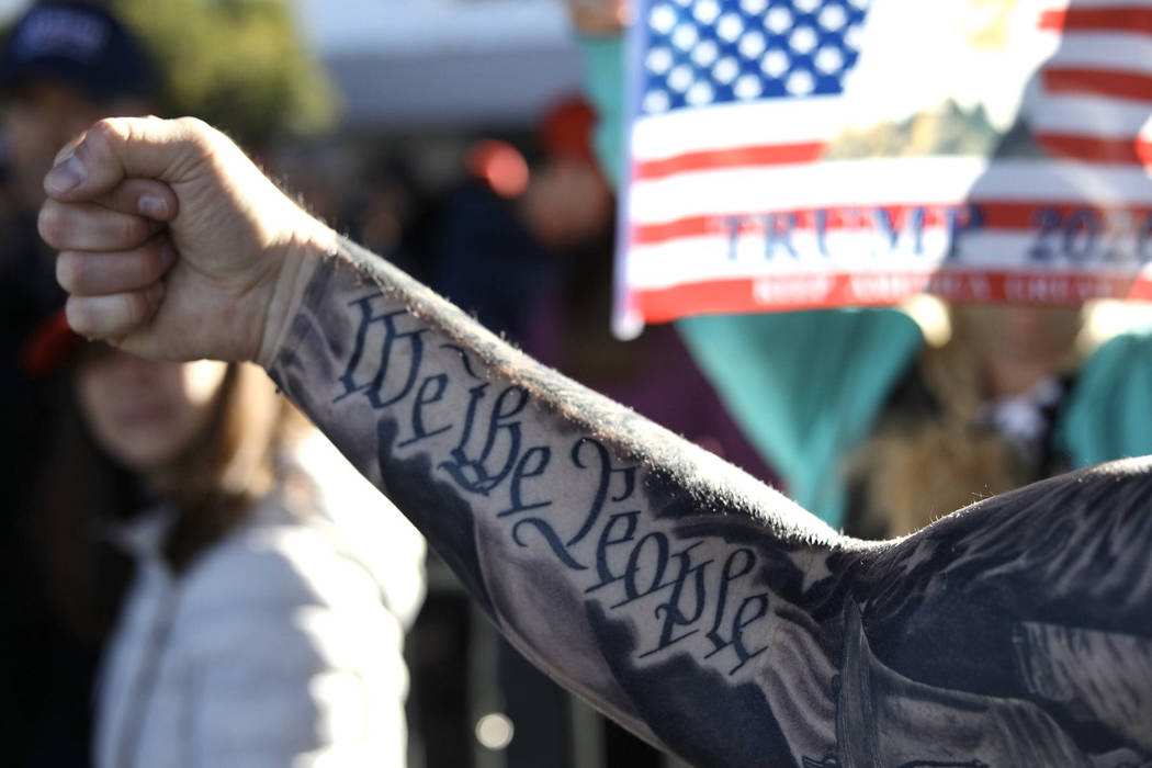 Doug Durbin of Las Vegas shows off his tattoo before a President Trump campaign rally Friday, F ...