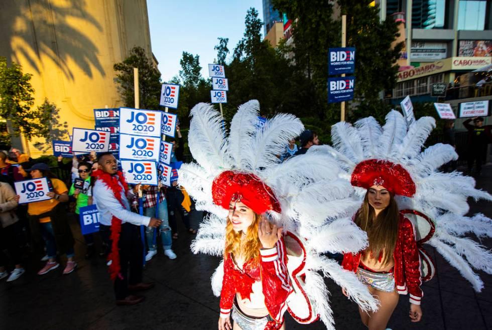 Showgirls walk past supporters of Democratic presidential candidate Joe Biden ahead of the Demo ...