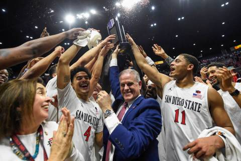 San Diego State head coach Brian Dutcher, center, and players hold up the Mountain West Champio ...