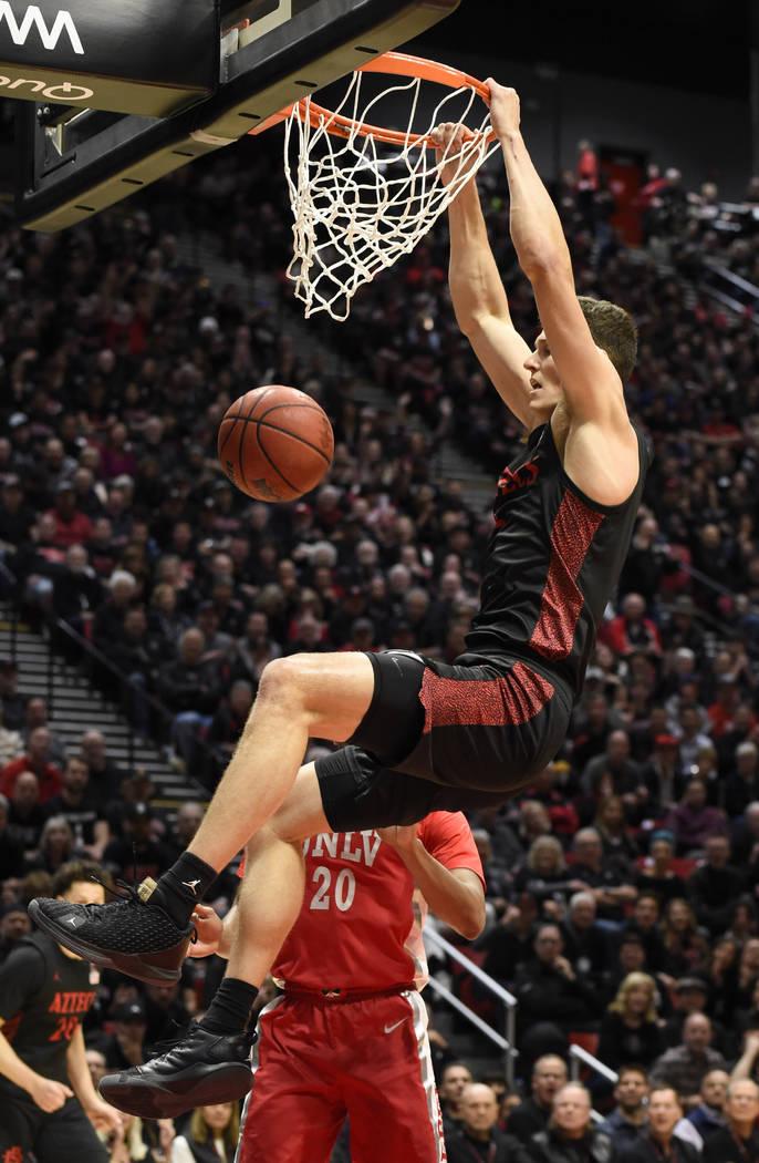 San Diego State forward Yanni Wetzell, top, dunks as UNLV forward Nick Blair (20) looks on duri ...