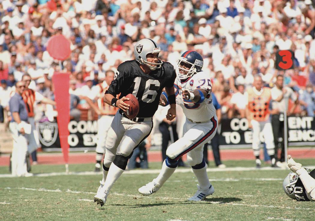 Los Angeles Raiders quarterback Jim Plunkett (16) is dogged by New York Giants George Martin du ...