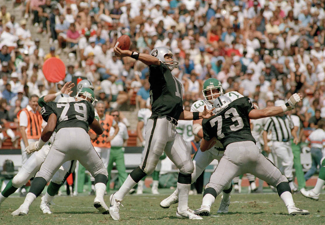 Jim Plunkett, Los Angeles Raiders quarterback winds up to let loose pass to wide receiver Dokie ...