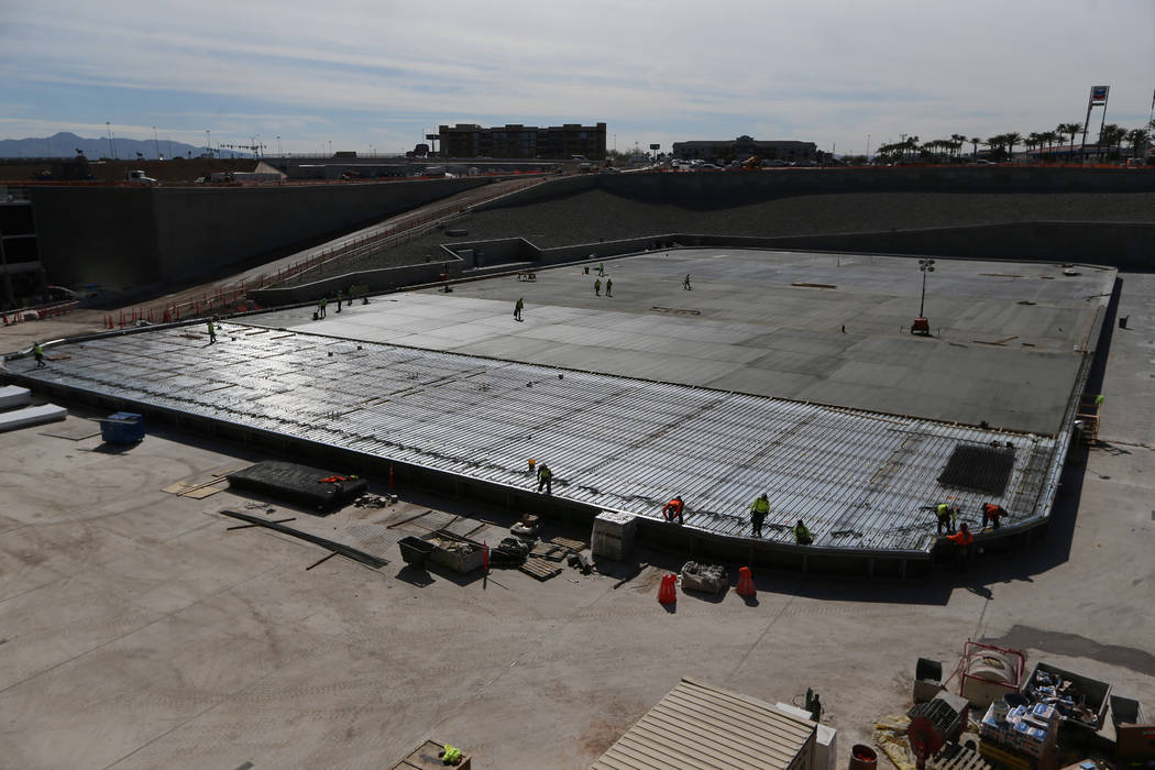 Construction workers prepare a section of the field tray to pour cement at the Raiders Allegian ...