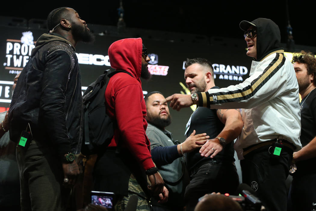 Tyson Fury, right, gestures at Deontay Wilder during a press conference at the MGM Grand Garden ...
