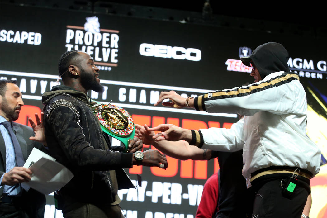 Tyson Fury, right, shoves Deontay Wilder during a press conference at the MGM Grand Garden Aren ...