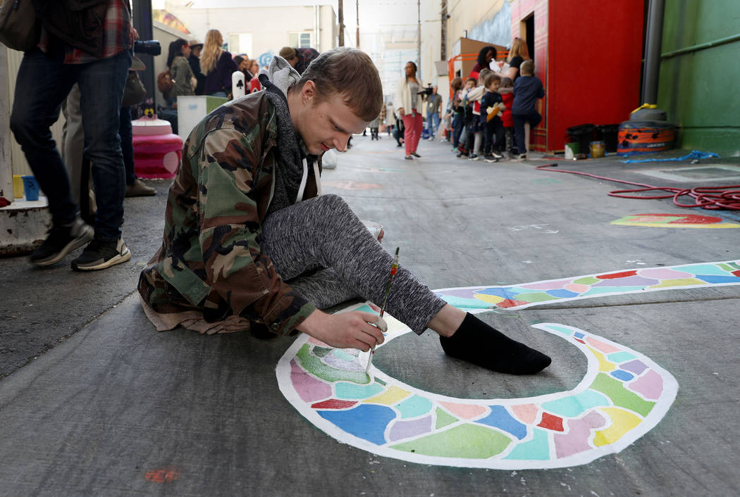 Local muralist Hunter Wilson paints during the grand opening of dT-Alley in Las Vegas on Thursd ...