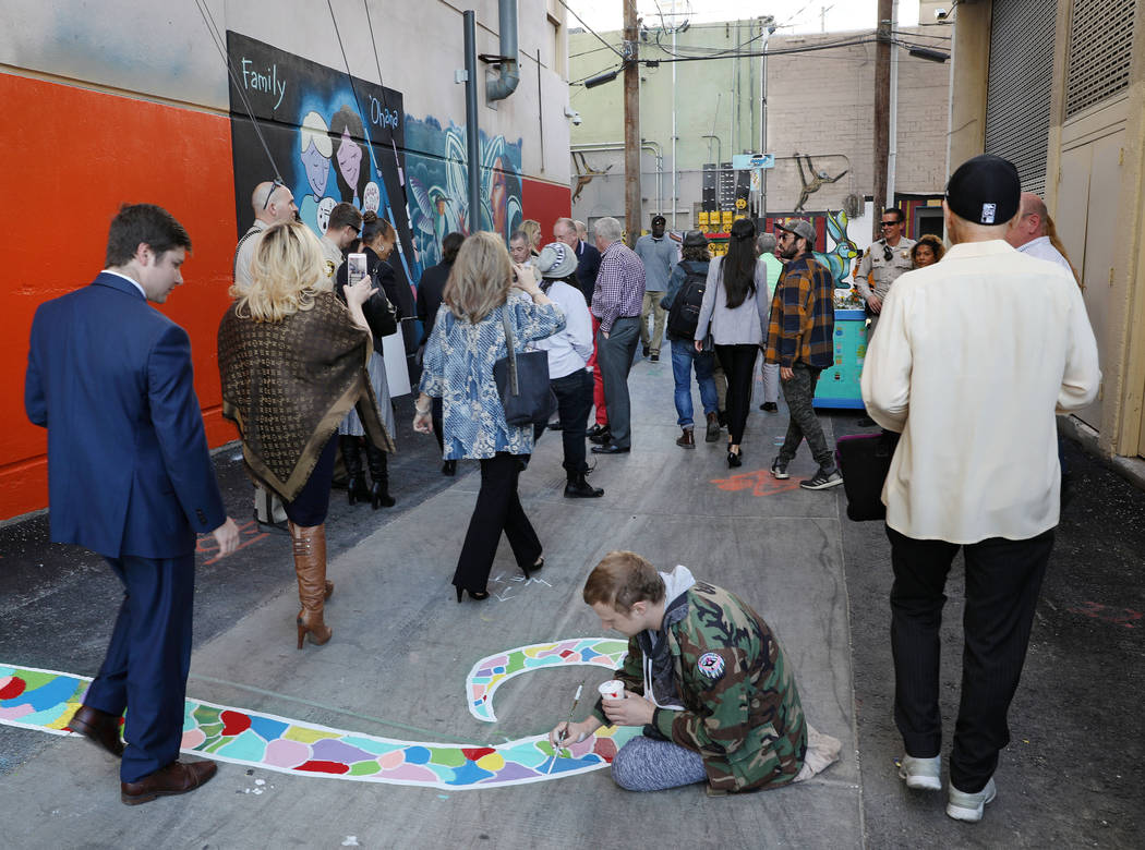 Individuals walk through the grand opening of dT-Alley as local muralist Hunter Wilson paints, ...
